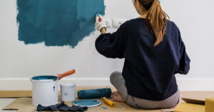 Young woman painting a wall blue