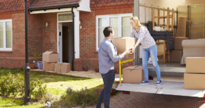 Man and woman unloading moving boxes in the back of a removalist truck